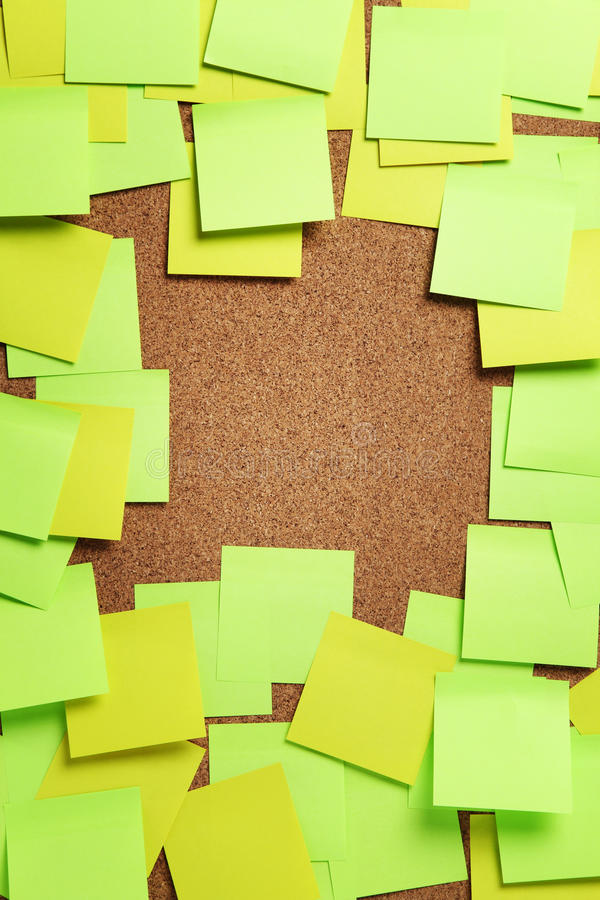Image of blank green and yellow sticky notes on cork bulletin bo. Ard with copyspace royalty free stock photography
