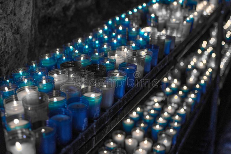 Image bleue désaturée d'un plan rapproché des bougies colorées brûlant dans le tunnel de Covadonga, Cangas de Onis, Asturies, Esp photo stock