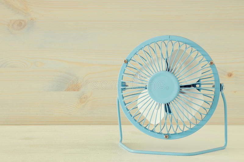 Image of blue retro fan on white wooden table. Vintage filtered royalty free stock photography