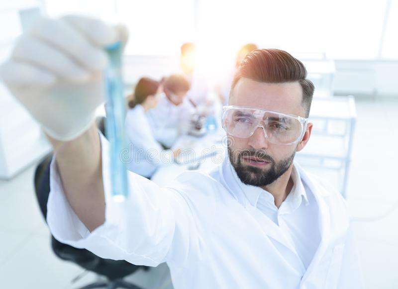 Image is blurred. young scientist holding tube with the reagents royalty free stock photography