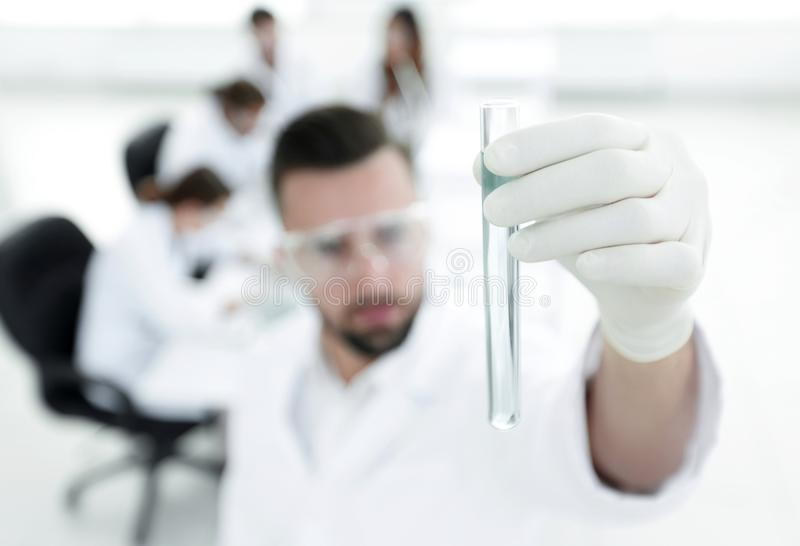 Image is blurred. young scientist holding tube with the reagents stock image
