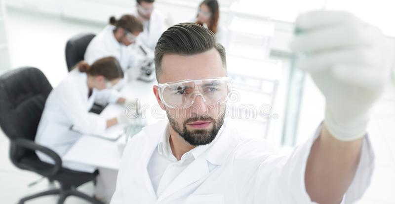 Image is blurred. young scientist holding tube with the reagents stock photography