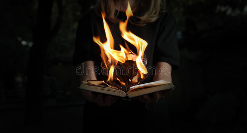 Image of book burning in woman hands in forest stock photography