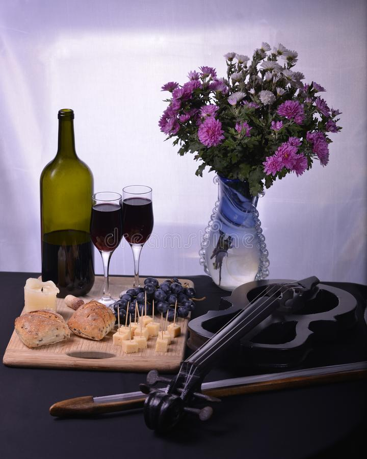 Image bottle of wine candle bread grapes and cheese violin flowers royalty free stock photos