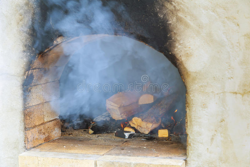 Image of a brick pizza oven with fire stock images