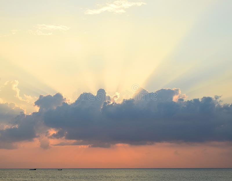 Skyscape at time of Sunset - Crepuscular Bright Sunrays spreading through Clouds with Orange sky at Horizon over Blue Sea Water stock image