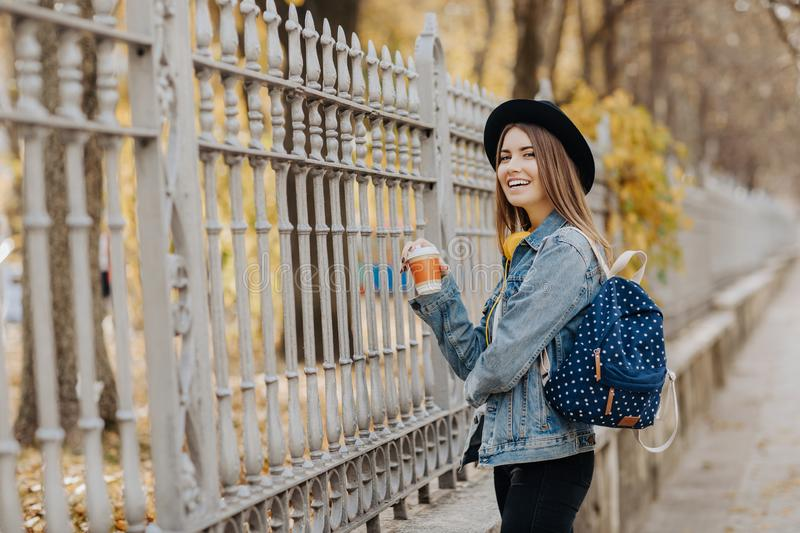 Image of a bright smiling hipster girl with brown hair wearing a hat and backpack holding cup of tea or coffee in the stock image