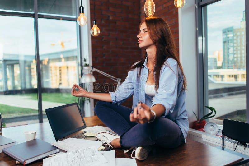 Image brouillée d'étudiante méditant sur le bureau dans l'esprit apaisant de salle de classe avec sa main au foyer image libre de droits