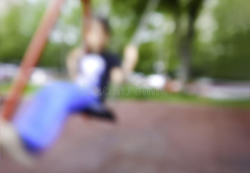 Image brouillée d'enfant de garçon balançant sur enfant en bas âge de terrain de jeu de parc de chaise d'oscillation le jeune deh images libres de droits