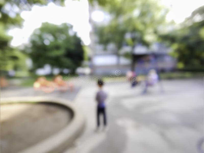 Image brouillée d'enfant solitaire dans de terrain de jeu seul de parc le garçon se tenant sur l'espace urbain de jeu de la ville image stock
