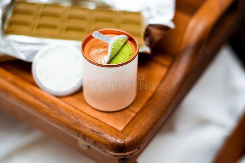 Image brouillée de defocus avec une boîte ouverte cylindrique avec le match chinois vert de poudre de thé photo stock
