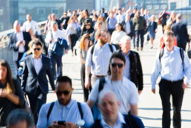 Image brouillée des employés de bureau croisant le pont de Londres dans le début de la matinée sur le chemin à la ville de Londre photo libre de droits