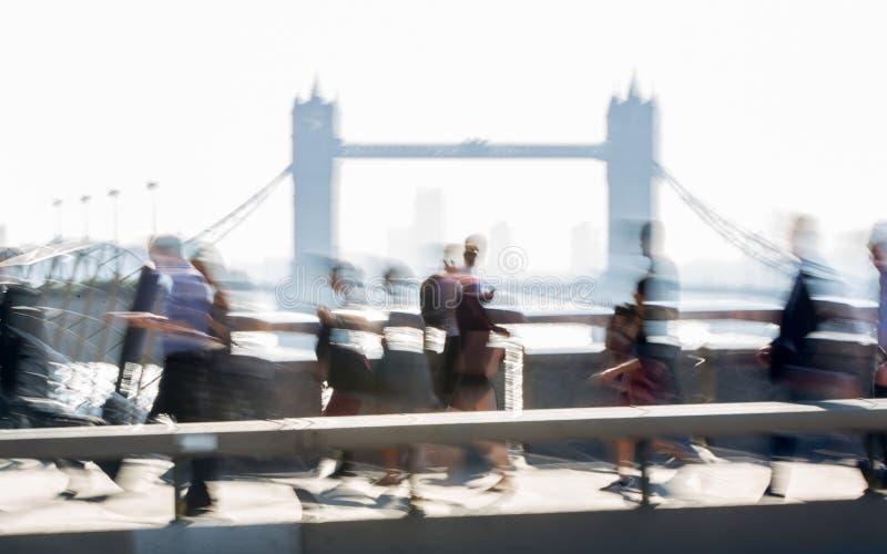 Image brouillée des employés de bureau croisant le pont de Londres dans le début de la matinée sur le chemin à la ville de Londre photos libres de droits