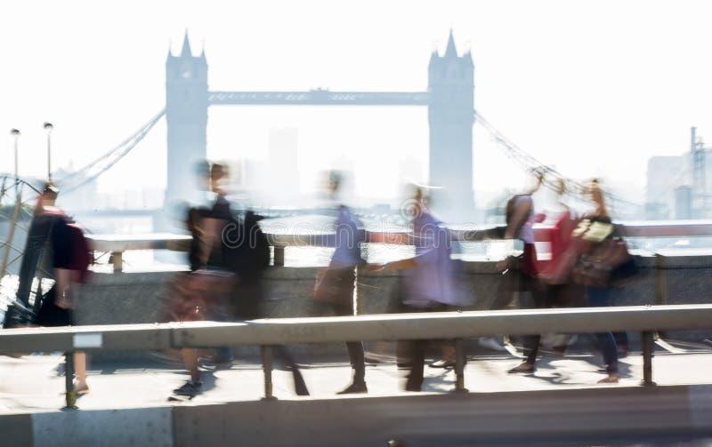 Image brouillée des employés de bureau croisant le pont de Londres dans le début de la matinée sur le chemin à la ville de Londre image stock