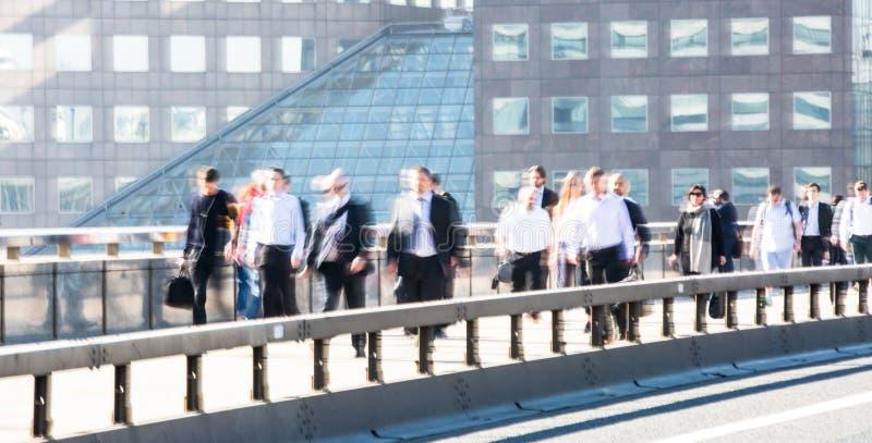 Image brouillée des employés de bureau croisant le pont de Londres dans le début de la matinée sur le chemin à la ville de Londre image libre de droits
