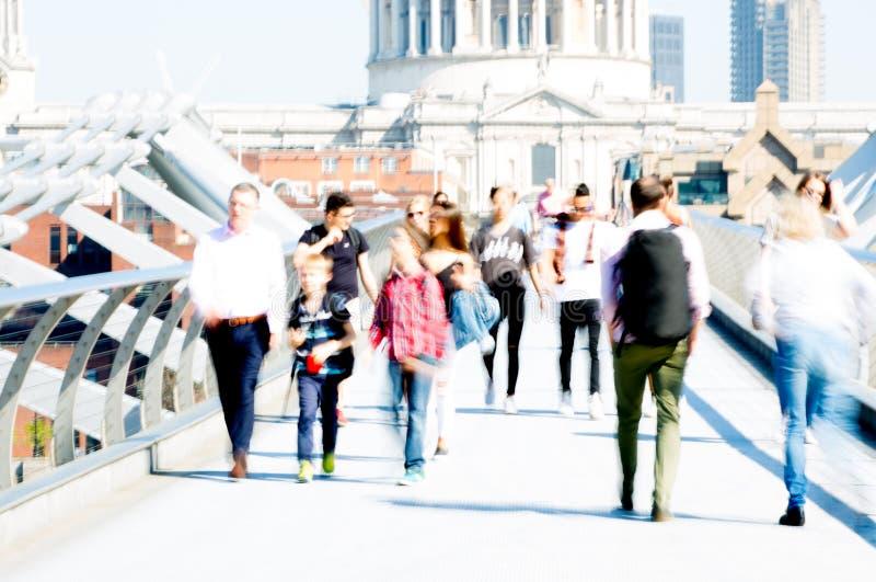 Image brouillée des employés de bureau croisant le pont de millénaire dans le début de la matinée sur le chemin à la ville de Lon image stock