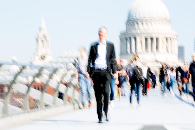 Image brouillée des employés de bureau croisant le pont de millénaire dans le début de la matinée sur le chemin à la ville de Lon photographie stock