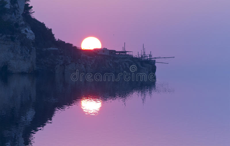 Image brouillée des réflexions sur la mer au coucher du soleil avec le centre mou du soleil et du trabocco photo stock