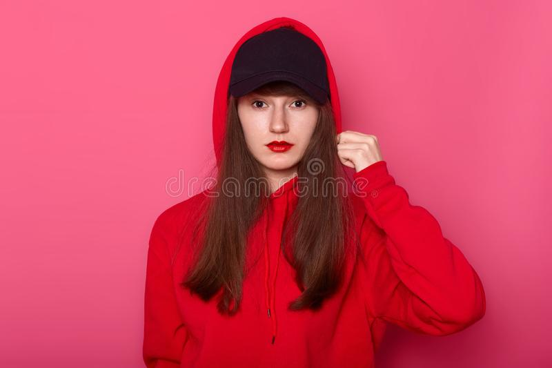 Image of brunette girl looking directly at camera with calm facial expression, wearing casual red hoody and black cap, touches her stock photos
