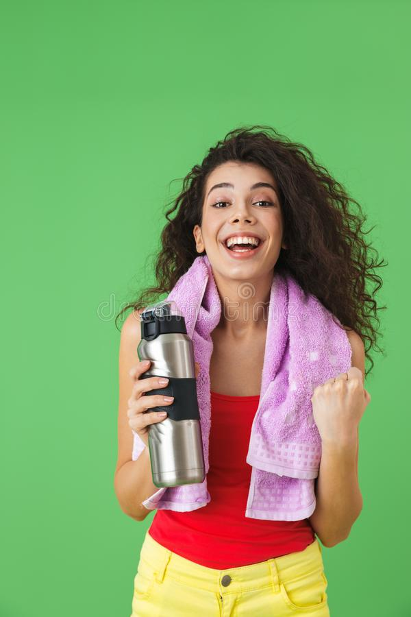 Image of brunette woman 20s in sportswear rejoicing and drinking water after training royalty free stock photo