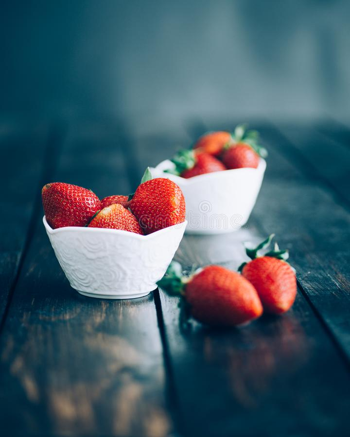Fresh strawberries in white bowl on old wooden table stock image