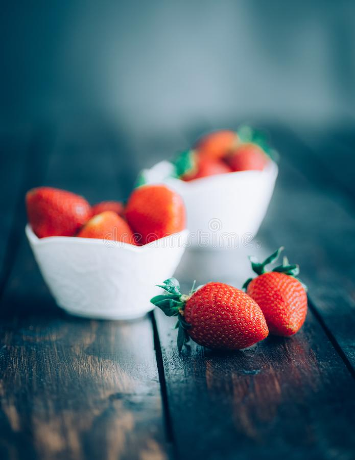 Fresh strawberries in white bowl on old wooden table stock photo
