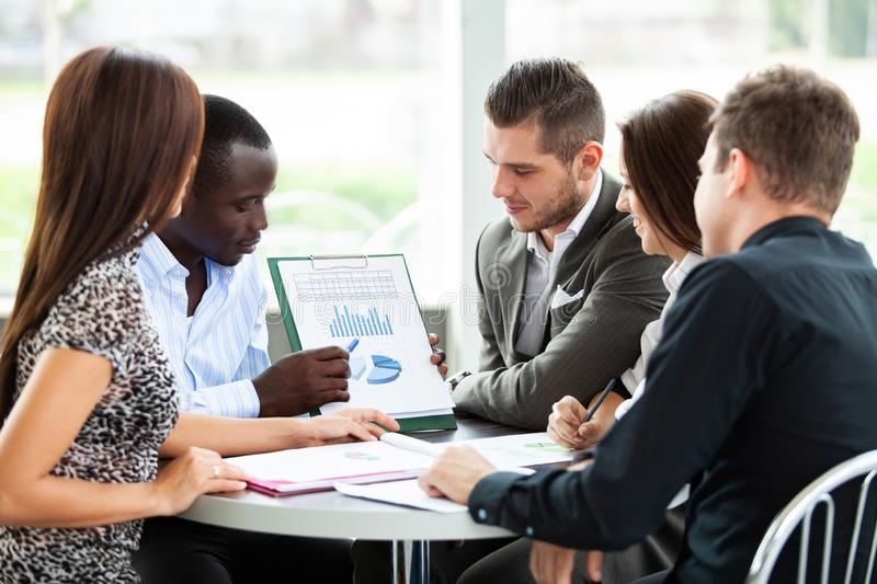 Image of business partners discussing documents and ideas at meeting. royalty free stock image