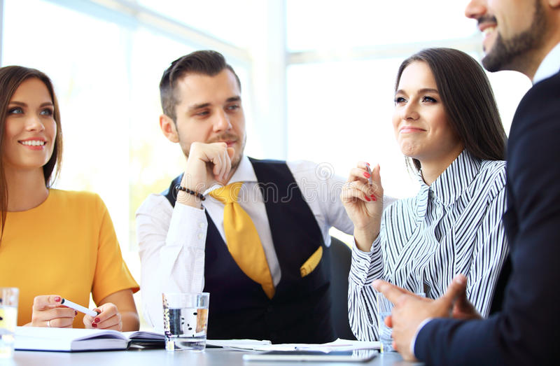 Image of business partners discussing documents and ideas stock image