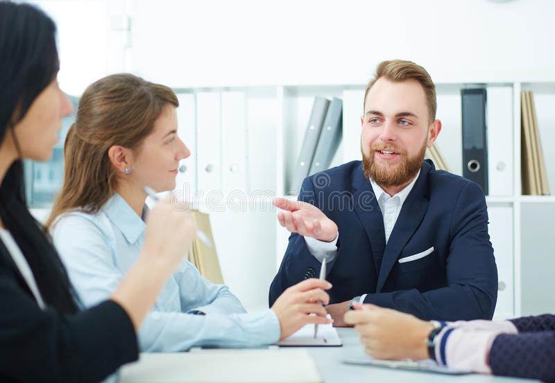 Image of business partners discussing documents and ideas at meeting. stock photography