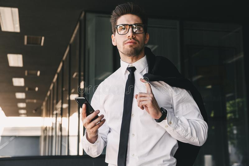 Image of businesslike man dressed in formal suit standing outside glass building with jacket over his shoulder, and holding mobil. Image of businesslike man royalty free stock photos