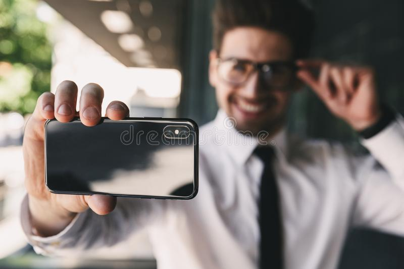 Image of businesslike man dressed in formal suit standing outside glass building, and taking selfie photo on smartphone. Image of businesslike man dressed in stock photos
