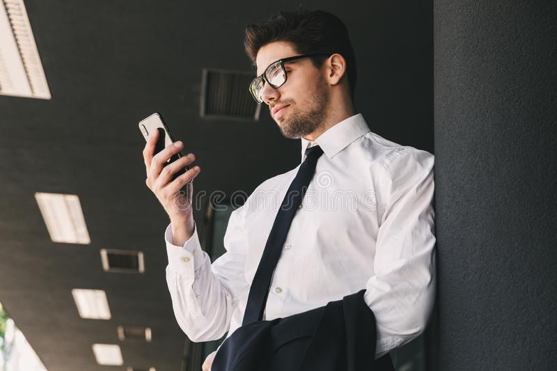 Image of businesslike man dressed in formal suit standing outside glass building, and using smartphone. Image of businesslike man dressed in formal suit standing royalty free stock photography