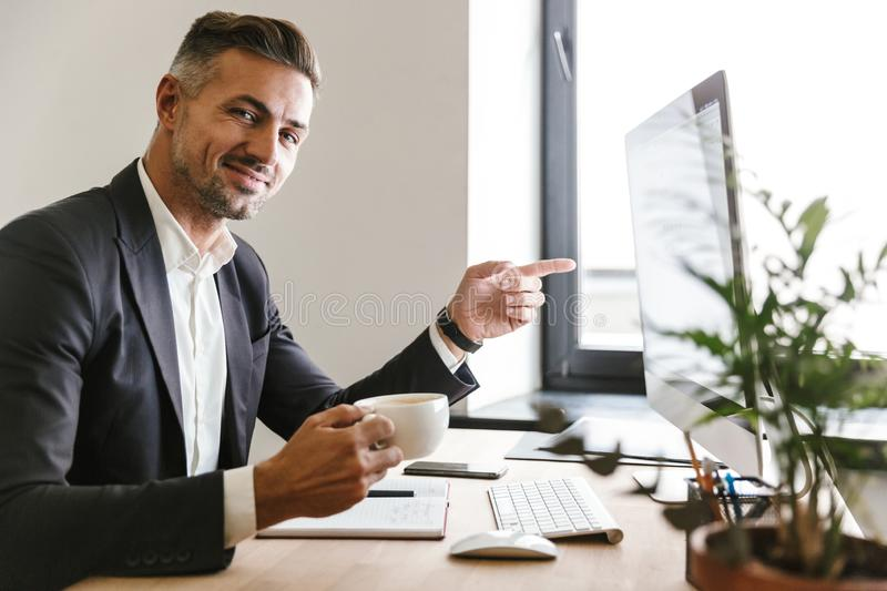 Image of businesslike man drinking coffee while working on computer in office. Image of businesslike man 30s wearing suit drinking coffee while working on stock images