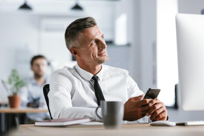 Image of businesslike man 30s wearing white shirt and tie sitting at desk in office by computer, and holding smartphone. Image of businesslike man 30s wearing royalty free stock photography