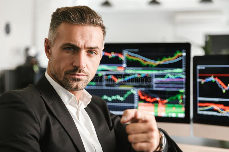 Image of businesslike man working in office on computer with graphics and charts at screen. Image of businesslike man 30s wearing suit working in office on stock image