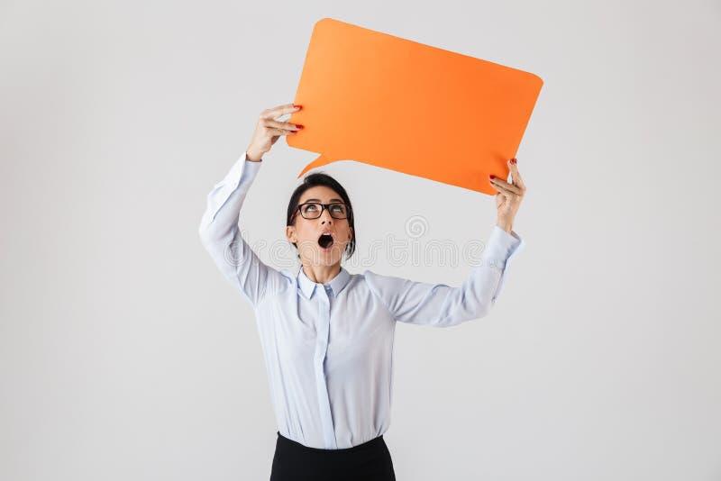 Image of businesslike office woman wearing eyeglasses holding yellow copyspace placard, isolated over white background. Image of businesslike office woman stock photo