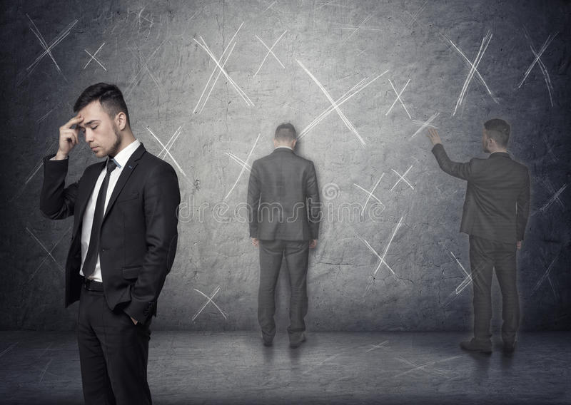 Image of businessman thinking about how to solve problem with 'x' marks around him stock photography