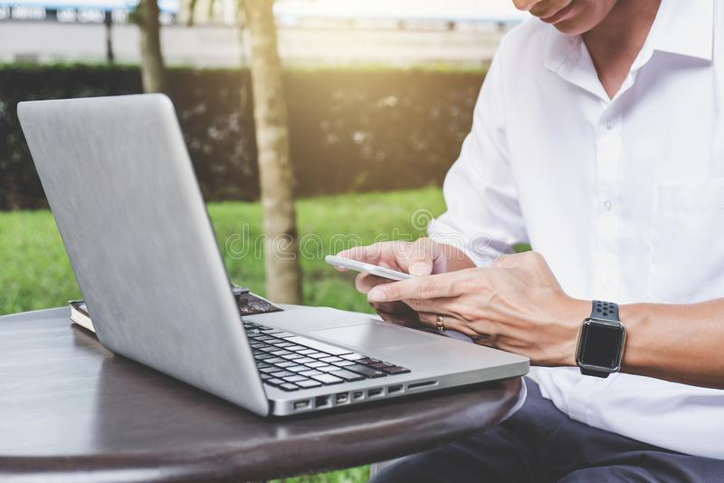 Image of businessman working with laptop and analysis financial. Document data on smartphone in outdoor office, finance,investment, business concept and stock photos