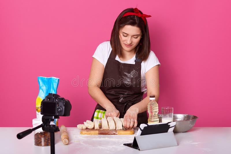 Image of busy skillful baker standing isolated over pink background in studio, spending time at kitchen, working hard, cutting. Dough with knife to pieces stock images