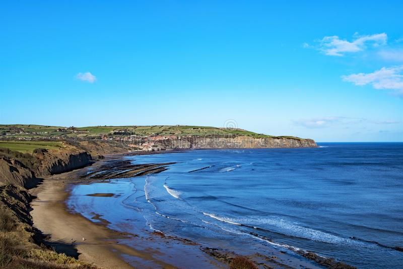 Cleveland Way view of Boggle Hole beach and Robin Hood`s Bay. This image captured on the Cleveland Way cliff top walk, shows the tide coming into Boggle Hole royalty free stock photo