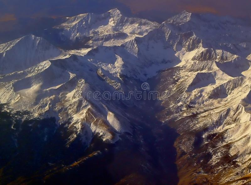 Image captured from a window of a commercial airplane while flying over western United States. Mountain range royalty free stock photo