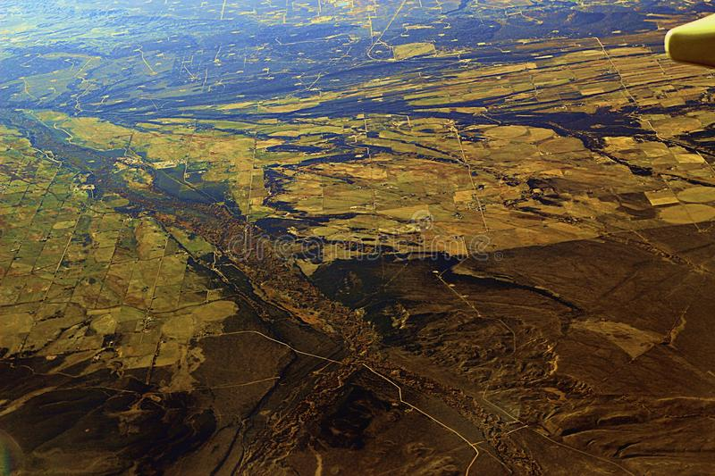 Image captured from a window of a commercial airplane while flying over western United States. Rural area royalty free stock photo