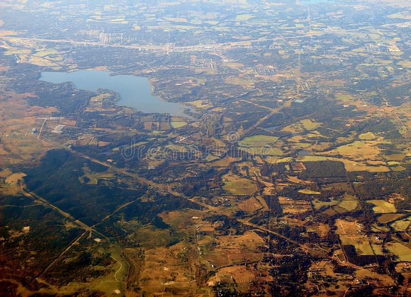 Image captured from a window of a commercial airplane while flying over western United States. Urban area with a lake stock image