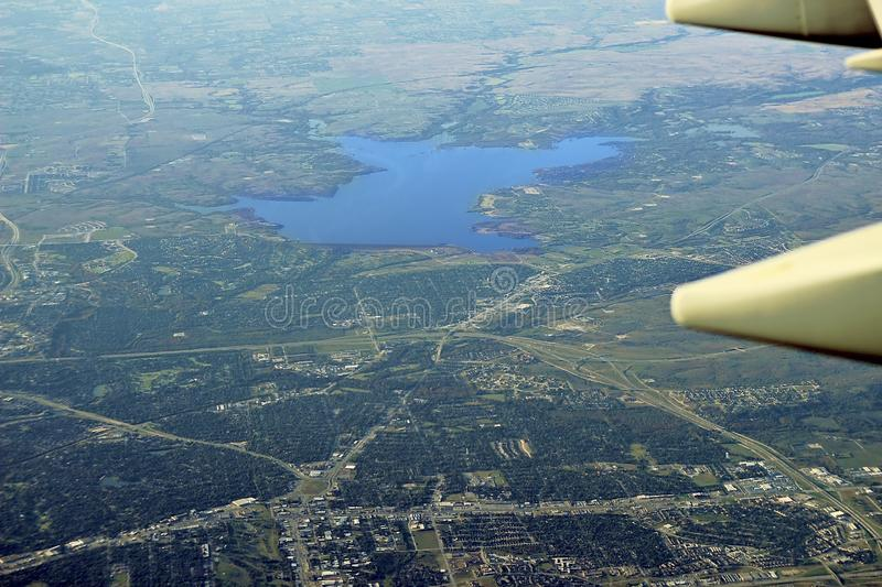 Image captured from a window of a commercial airplane while flying over western United States. Urban area with a lake royalty free stock image
