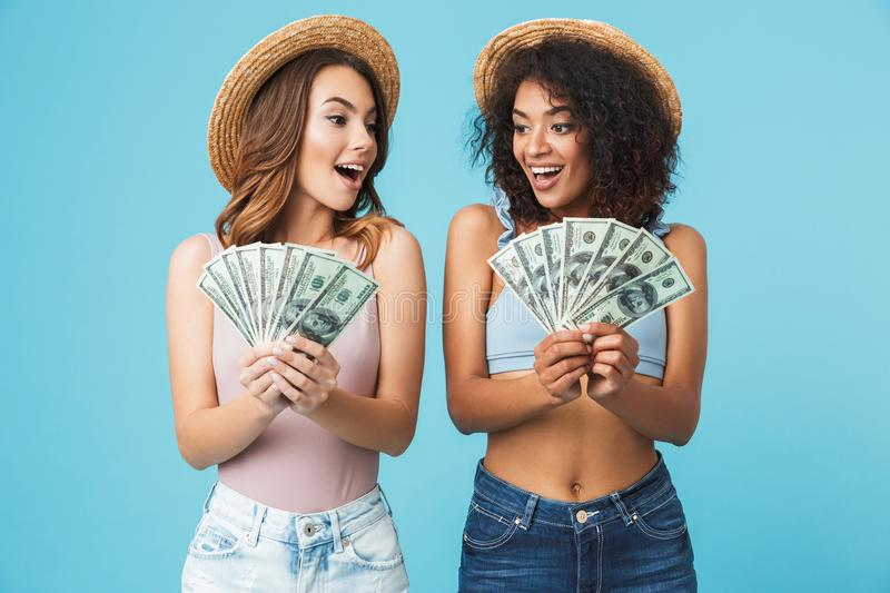 Image of caucasian and african american women wearing straw hats. And summer clothing looking at many dollar banknotes holding in hands isolated over blue royalty free stock image