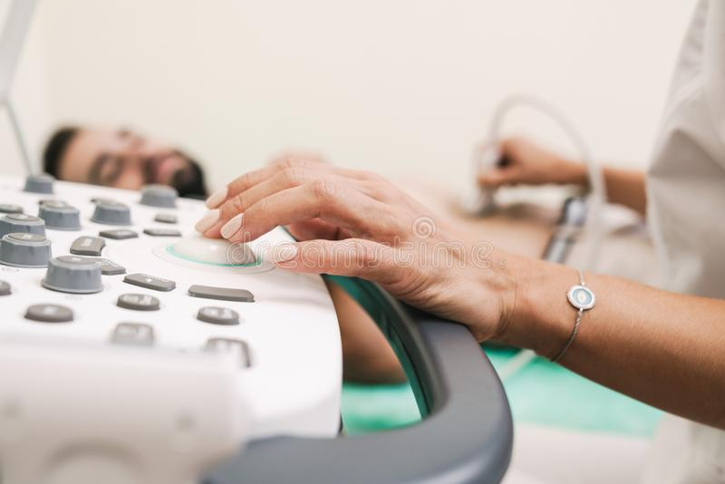 Image of caucasian man getting abdominal ultrasound scan by female doctor stock photos