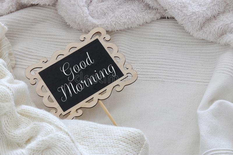 Image of chalkboard with text: GOOD MORNING over cozy and white blanket. Top view. royalty free stock image