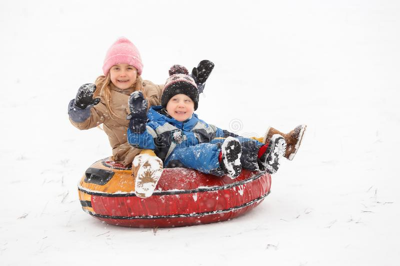 Image of cheerful girl and boy riding tubing stock images