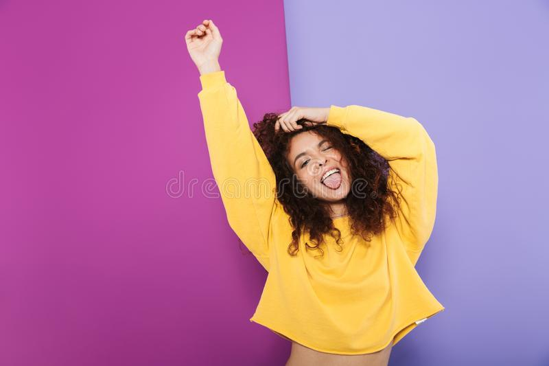 Image of cheerful happy curly woman swearing casual clothes showing tongue at camera and dancing stock photo