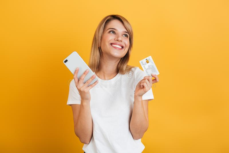 Happy young blonde woman posing isolated over yellow wall background dressed in white casual t-shirt using mobile phone holding stock images